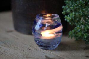 Glazen waxinelichthouder of theelichthouder met in de bodem een beetje as