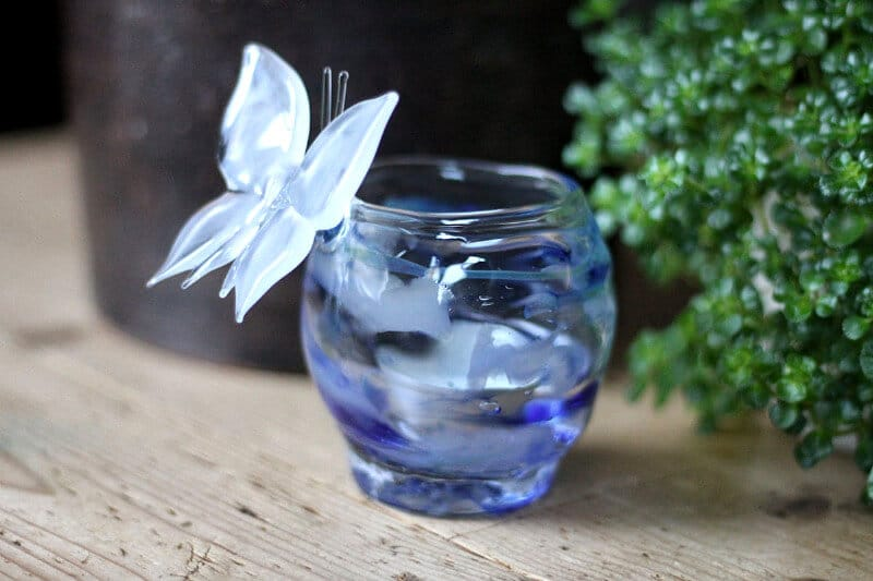 Glazen waxinelichthouder of theelichthouder met as en een vlinder